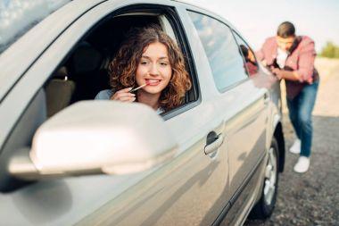 woman driving and man pushing car