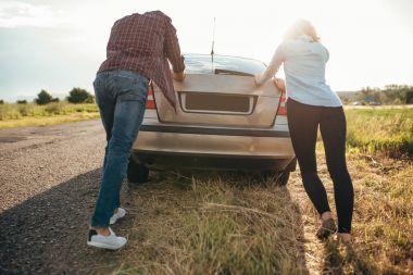 man and woman pushing broken car