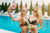 Fotografie zwei glückliche junge Frauen am Pool