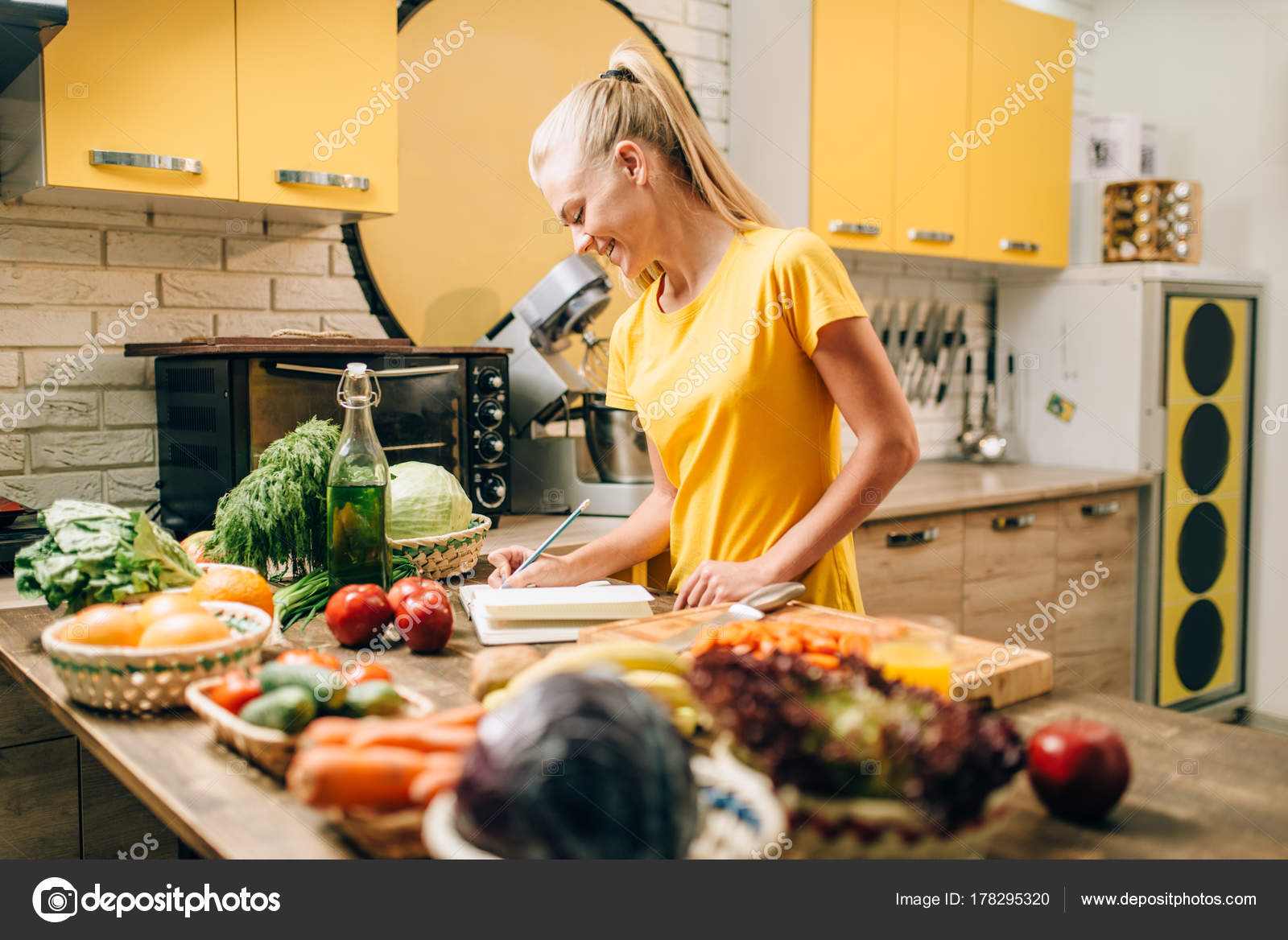 Young woman cooking kitchen writing recipe book healthy food young woman cooking kitchen writing recipe book healthy food vegetarian stock photo forumfinder Choice Image