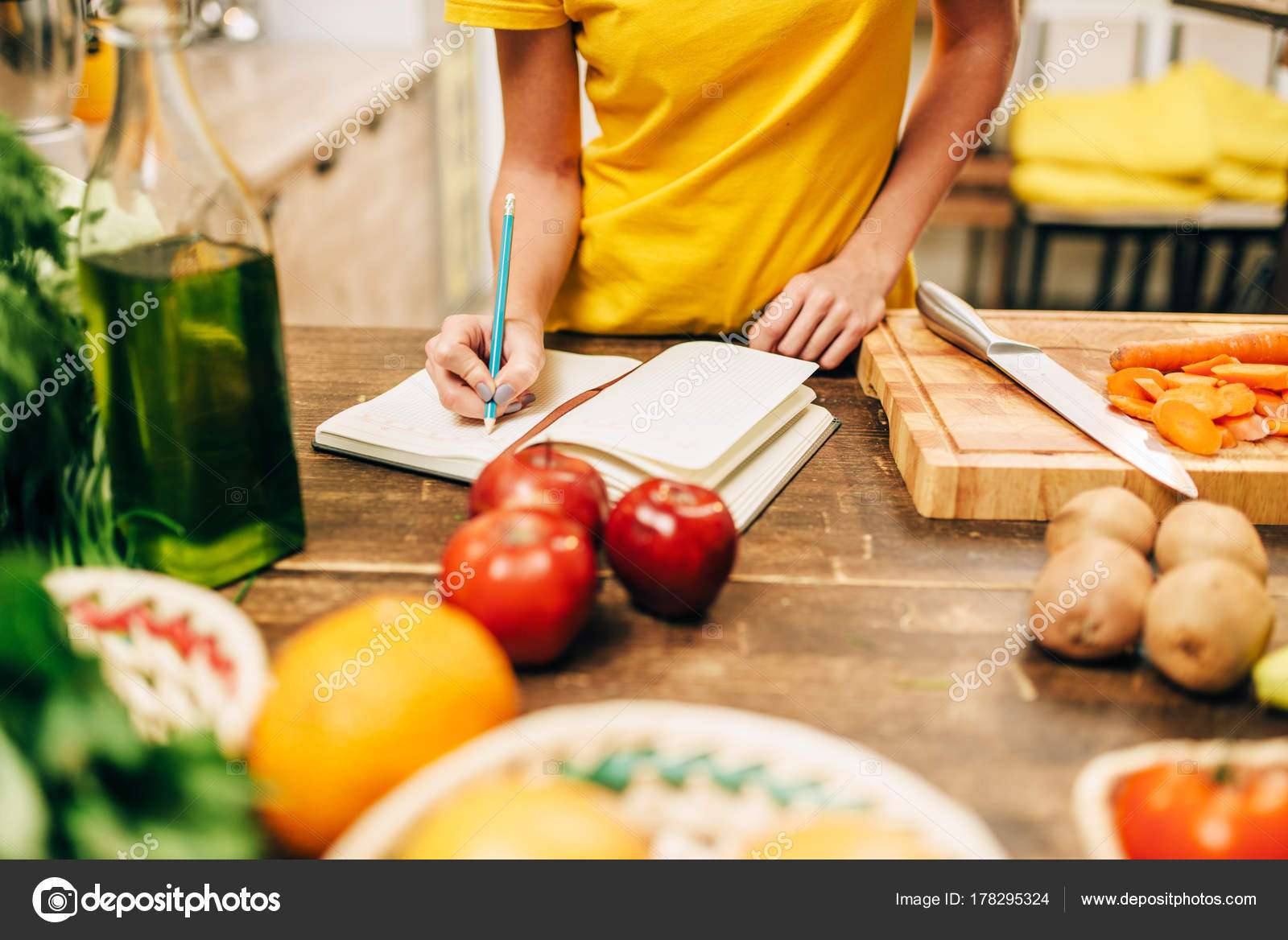 Young woman cooking kitchen writing recipe book healthy food young woman cooking kitchen writing recipe book healthy food vegetarian stock photo forumfinder Images