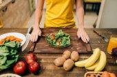 Žena, vaření salát v kuchyni, zdravé jídlo. Vegetariánská strava, čerstvá zelenina a ovoce na dřevěný stůl