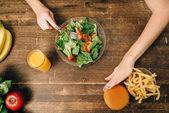 Fotografie žena jíst salát v kuchyni, vaření zdravých bio potravin. Vegetariánská dieta