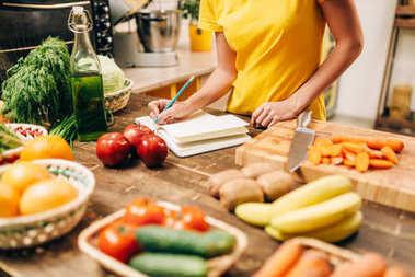 Young woman cooking in kitchen and writing in recipe book, healthy food. Vegetarian diet, fresh vegetables and fruits on the table