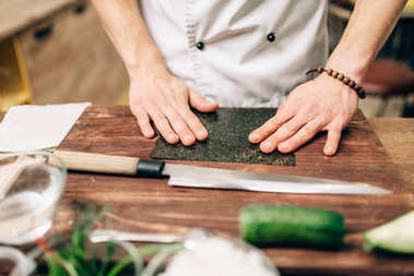 Male cook making sushi on wooden table. Traditional japanese cuisine, seafood