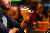 Fotografie mladý muž, který držel sklenici piva na baru v sport pub, šťastný rekreační fotbalový fanoušek