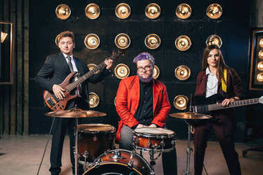 musicians in suits posing on stage with lights, retro style, guitarists and drummer, rock band