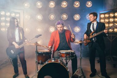 musicians in suits on stage with lights, retro style, guitarists and drummer, rock band