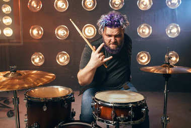 bearded drummer with colorful hair, rock performer showing devil horns gesture on the stage with lights. Music concert in night club