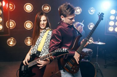 musicians on stage with lights, retro style, guitarists and drummer, rock band