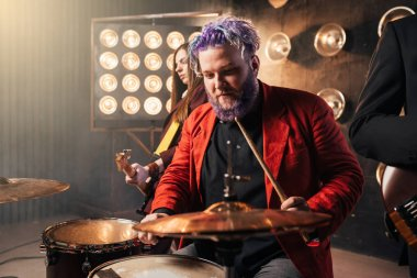 bearded drummer with colorful hair, rock performer in red suit on the stage with lights. Music concert in night club