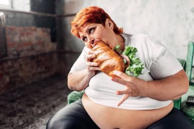 fat woman sitting in armchair and eating sandwich, unhealthy lifestyle and obesity concept