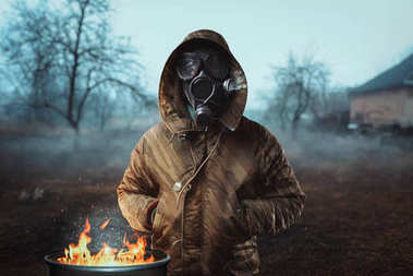 stalker soldier in gas mask near fireplace, survivor man after nuclear war. Post apocalyptic lifestyle