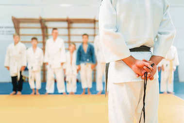 boys in kimono practicing martial art in sport gym with trainer