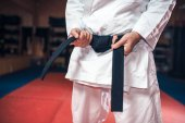 Photo fighter in white kimono with black belt, karate training in gym