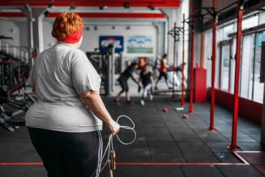 fat sweaty woman holding skipping with rope in gym