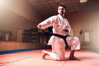 fighter in white kimono with black belt, karate training in gym