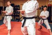 Fényképek Harcművészetek karate mester és a tanítványai fehér egyenruhát és fekete öves, harc képzés az edzőteremben