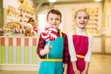 happy little cute children with lollipop in candy store
