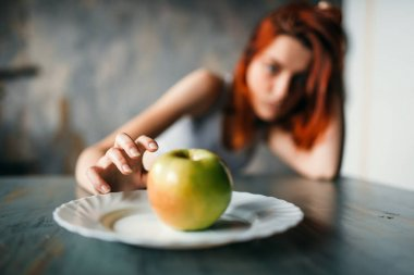 female hand reaching plate with apple, weight loss concept