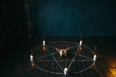 pentagram circle with candles on black wooden floor. Dark magic ritual with occult and esoteric symbols