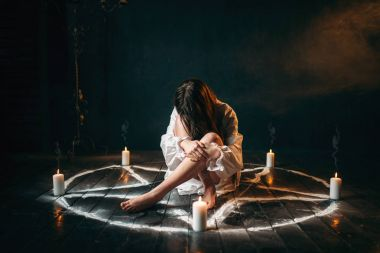 young woman in white shirt sitting in center of pentagram circle with candles, ritual of black magic, black wooden floor