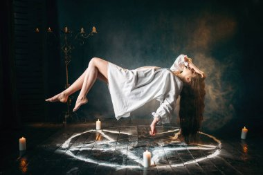 young woman in white shirt flying over pentagram circle, gark magic, sacrificial ritual. Occultism and exorcism