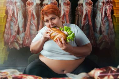 fat woman eating big burger against meat carcasses, overweight concept