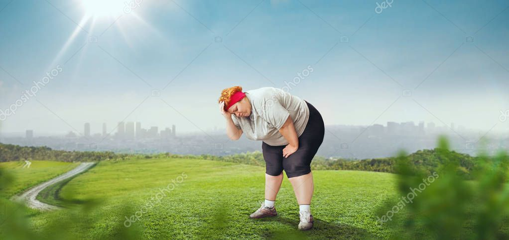 overweight woman tired after a run, green field and cityscape on background, female obesity, bulimic