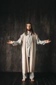 Fotografie Ježíš Kristus s otevřenou náručí, tmavé pozadí, křesťanskou víru, Boží syn