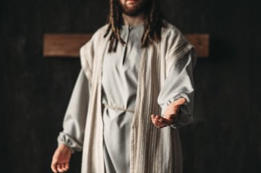 Jesus Christ reaching out hand, dark background, belief in god, christian faith