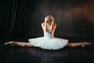 graceful and beautiful ballerina in white costume doing the splits in ballet class