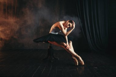 graceful and beautiful ballerina sitting on black banquette on the stage in theater