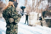 female paintball player with marker gun in hands, winter forest battle