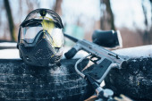 Splattered paintball mask with glasses and marker gun closeup. Extreme game equipment, sport ammunition