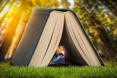 Reading concept, man sitting on the grass under large book and reads. Gaining knowledge from literature