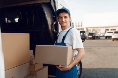 Smiling deliveryman with carton box at the car, delivery service. Man in uniform holding cardboard package, male deliver, courier job