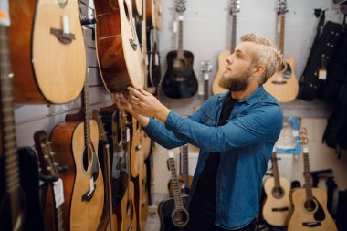 Bearded young man choosing acoustic guitar in music store. Assortment in musical instruments shop, male musician