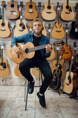Male guitarist plays on acoustic guitar in music store. Assortment in musical instruments shop, musician buying equipment