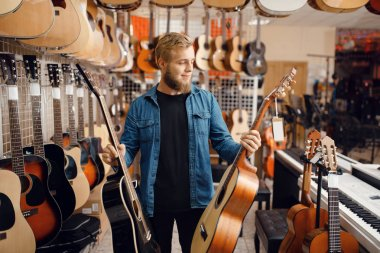 Bearded young guy choosing acoustic guitar in music store. Assortment in musical instruments shop, male musician buying equipment