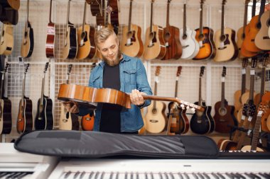 Male guitarist puts acoustic guitar in the case in music store. Assortment in musical instruments shop, musician buying equipment