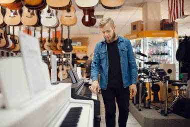 Male musician trying to play piano in music store. Assortment in musical instruments shop, keyboardist buying equipment, pianist in market