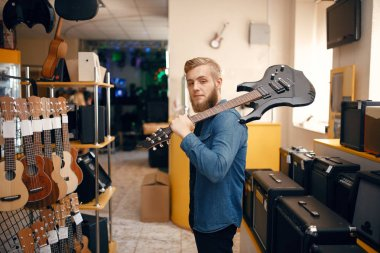 Young man poses with electric guitar on his shoulder in music store. Assortment in musical instruments shop, male musician buying equipment