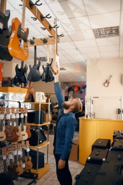 Bearded young man choosing acoustic guitar in music store. Assortment in musical instruments shop, male musician buying equipment