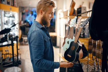 Bearded young man choosing ukulele guitar in music store. Assortment in musical instruments shop, male musician buying equipment