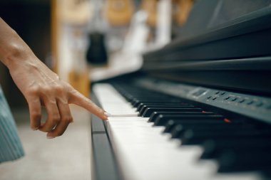 Young woman choosing digital piano in music store. Assortment in musical instrument shop, female musician buying equipment