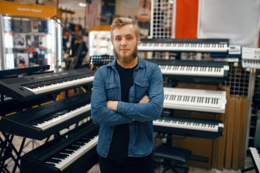 Bearded young man choosing synthesizer in music store. Assortment in musical instrument shop, male musician buying equipment