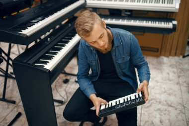 Bearded young musician buying synthesizer in music store. Assortment in musical instrument shop, male musician choosing keyboard