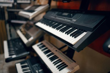 Digital synthesizers on showcase in music store, closeup view, nobody. Assortment in musical instrument shop, professional equipment for musicians and performers
