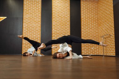 Two contemporary dance performers poses in studio. Female dancers  training in class, modern grace dancing, stretching exercise